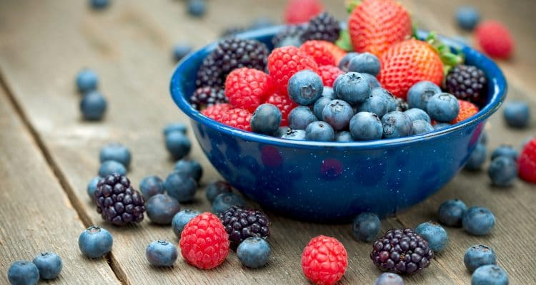 """A bowlful of delicious organic berries.  Strawberries, blackberries, blueberries and raspberries.  Shallow dof"""
